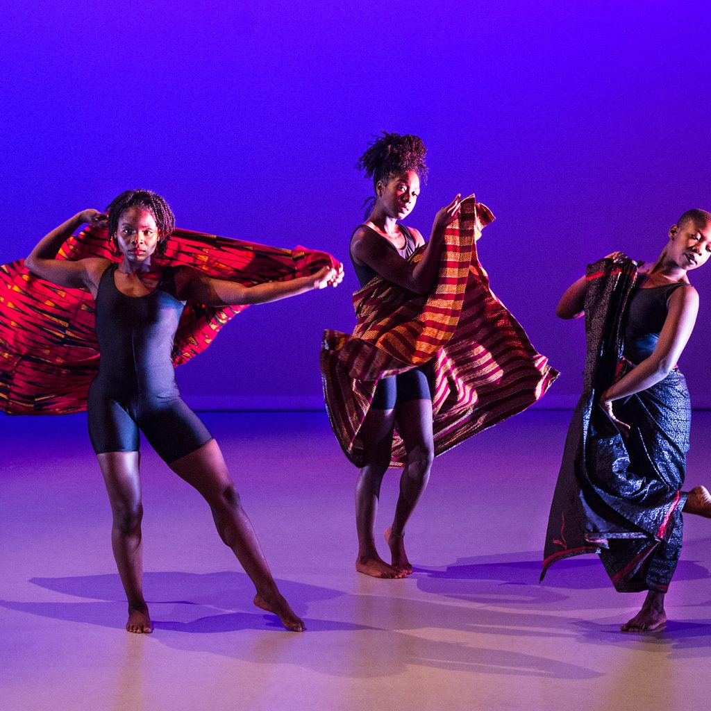 Three black, female dancers with head wraps under blue and purple lighting.