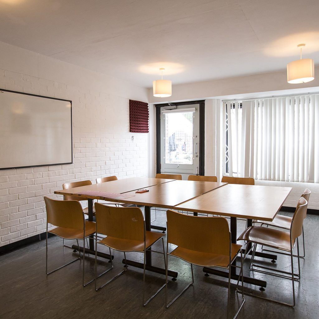 Meeting room with square table set for a meeting for 8.