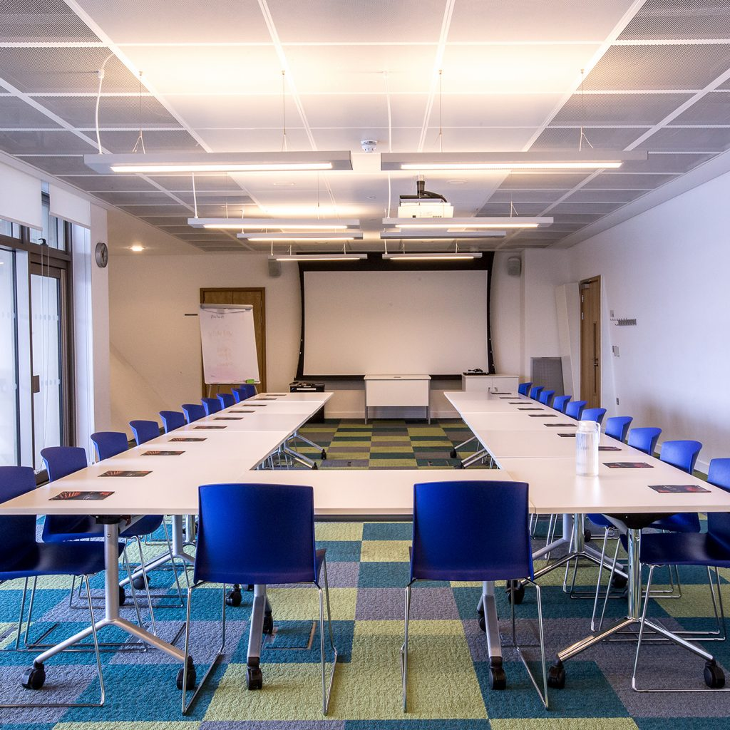 A large meeting room with tables in a U-shape and beautiful views of Canada Water.