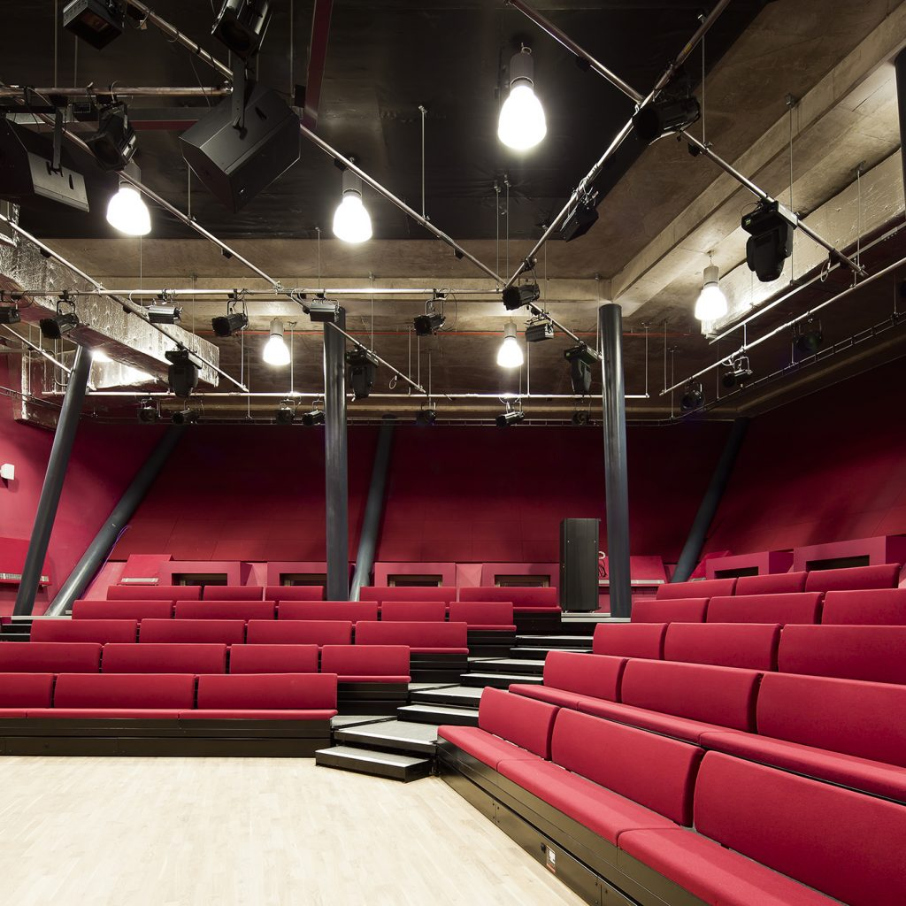 An intimate theatre space with red bench seating and a light, wood floor.
