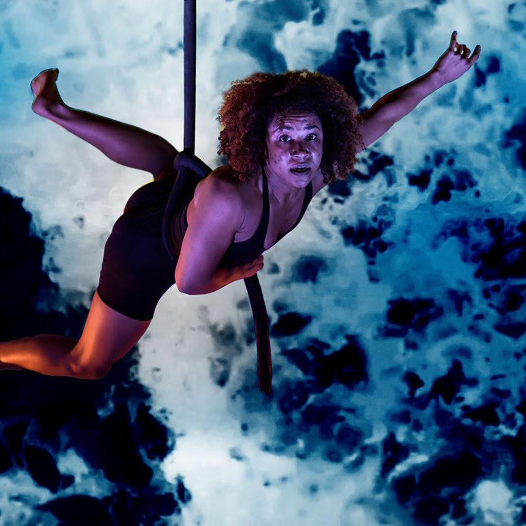 A female circus performer hangs from a rope which is around her waist. She is looking towards the camera.