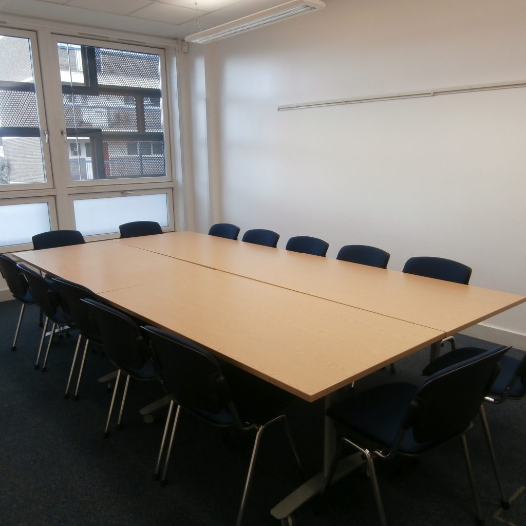 Meeting room with white walls, window at far end and tables and chairs in boardroom layout with 12 chairs