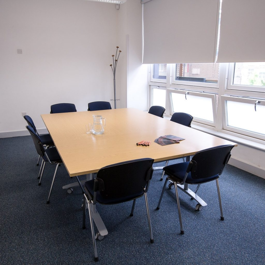 A small, bright meeting room with a large windo on the right and tables and chairs in boardroom style for 8