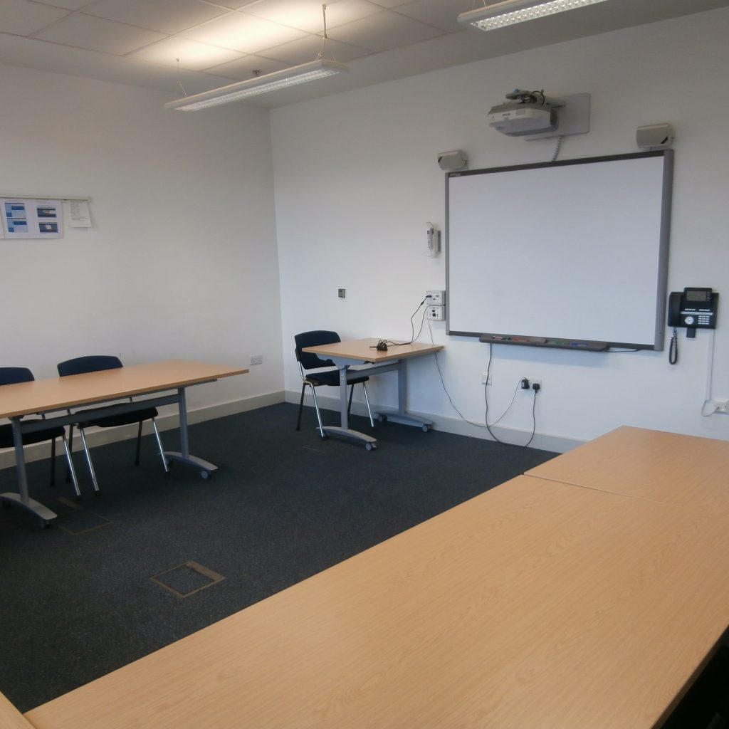Medium size meeting room with whiteboard at far end and tables in U-shape with chairs