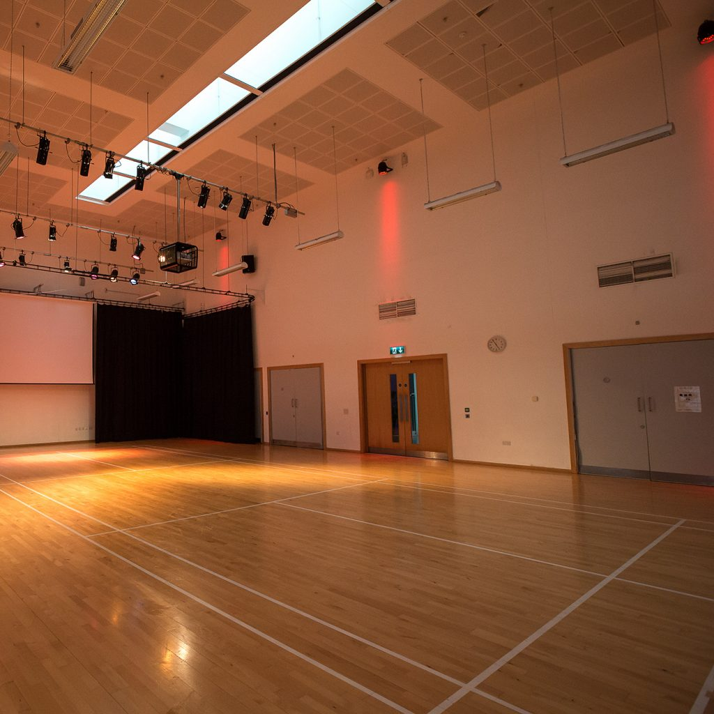 Large Hall with lighting rig, light wood floor and projection screen on the back wall.