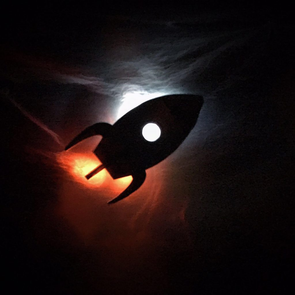 A shadow puppet of a rocket, lit by torchlight.