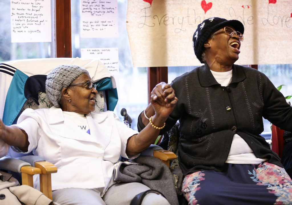Image shows two mature women of colour seated in comfy chairs holding hands and singing. There's a window with handwritten poetry and drawings pinned to it