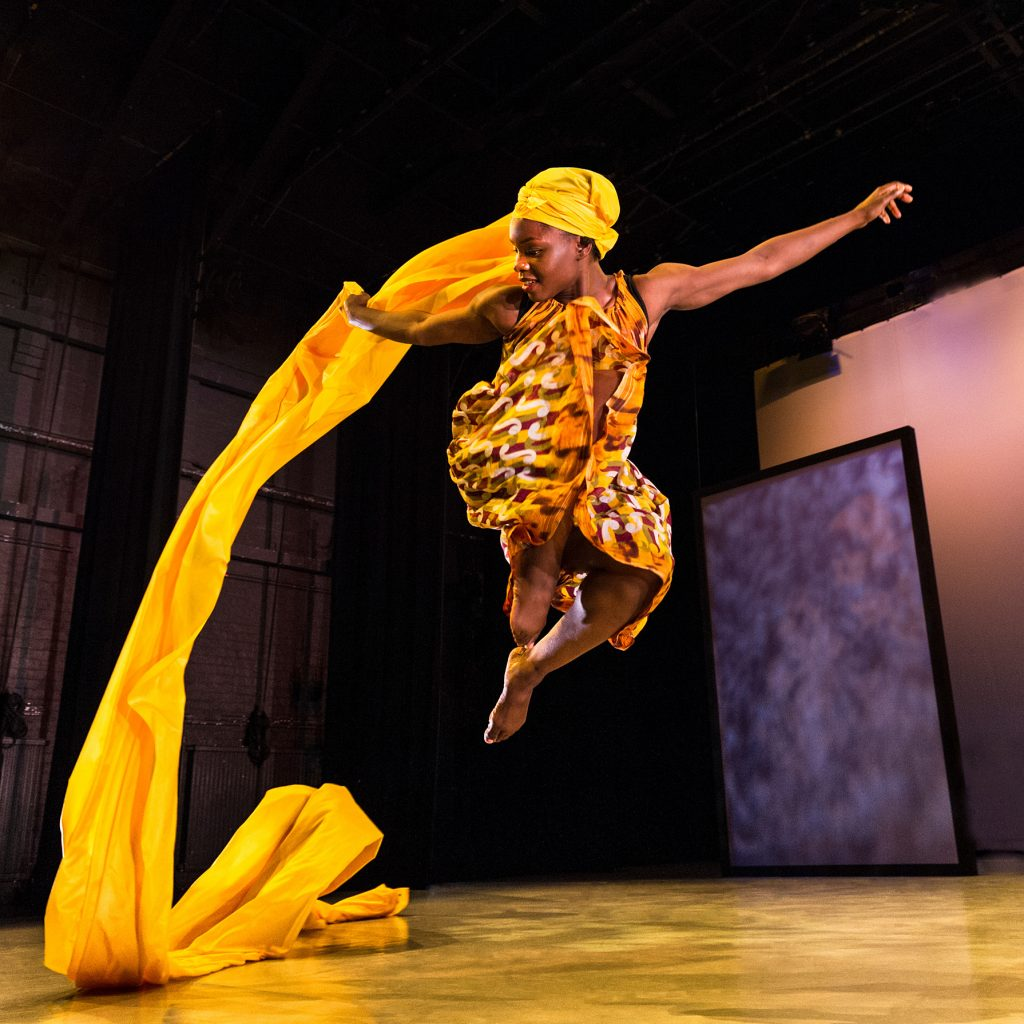 A female dancer with a bright yellow head wrap jumps in the air. The fabric flows out behind her from the wrap.