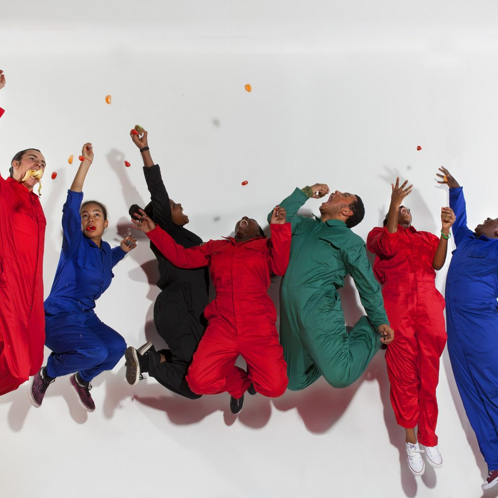 Seven young people in bright boiler suits leap in the air against a white background.