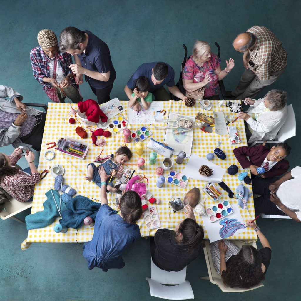 View of a table from above covered in craft materials with a baby lying on it and people of all ages stood and sat around it.