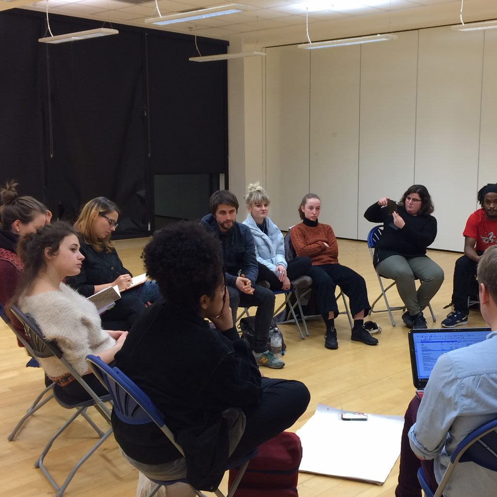Young people seated in a circle in a light coloured rehearsal room.
