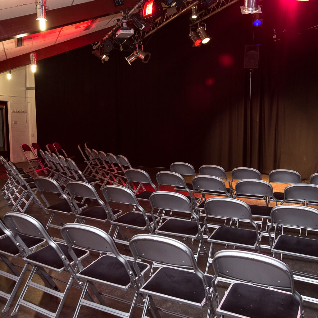 Rows of seats in a studio theatre with a black curtain at the back.