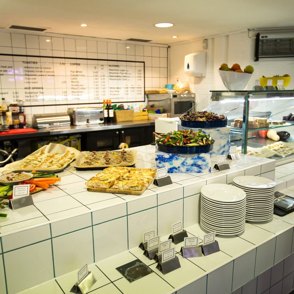 A white café counter with salads, quiche and crudite and dips on it.