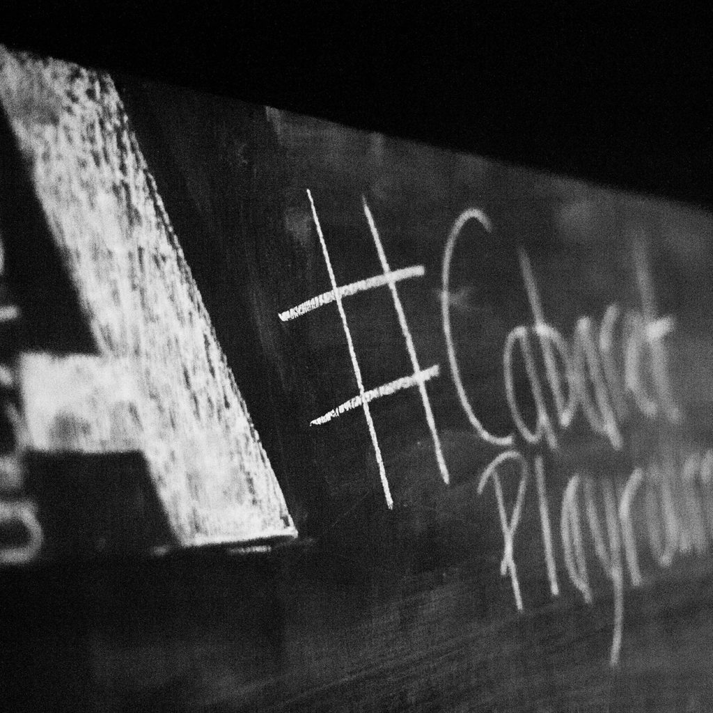 Black and white image of a blackboard with the Albany logo and Cabaret Playroom written on it.