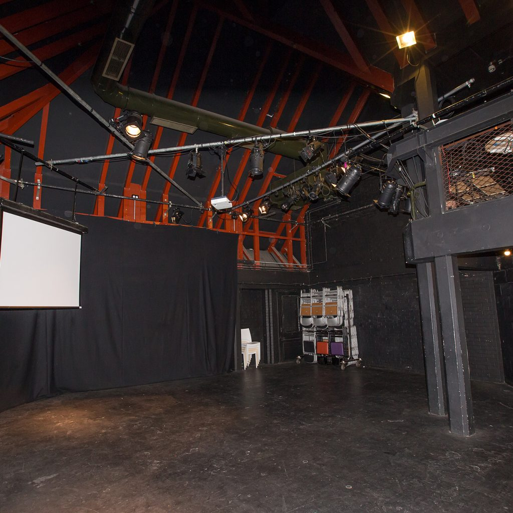 Image of small, empty theatre with full lighting rig.