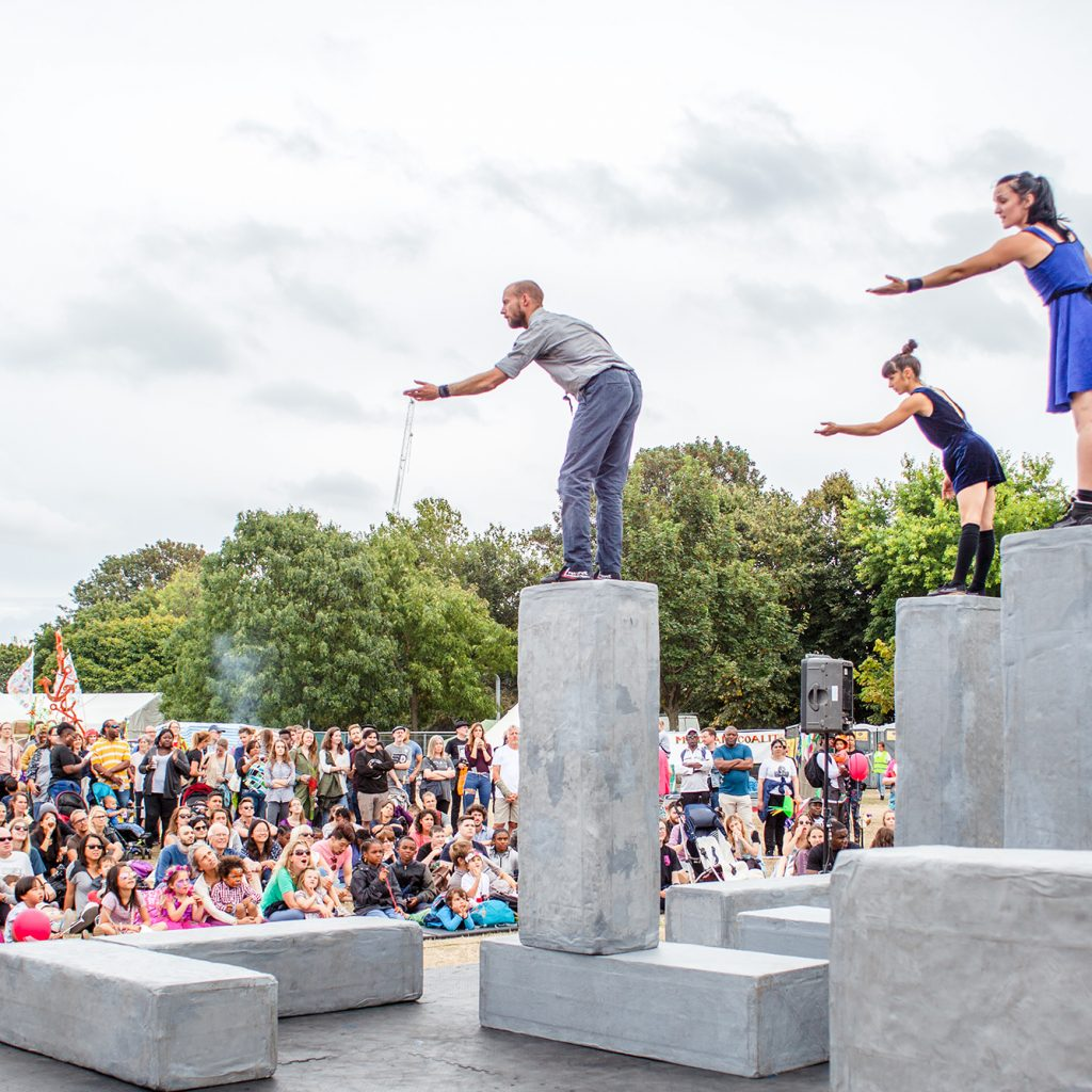 Circus performers stand balanced on large square blocks, looking out over a large crowd.