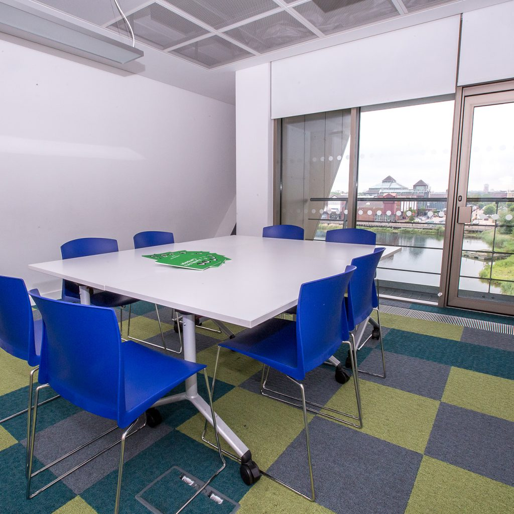 Meeting room set for eight people with view over Canada Water.