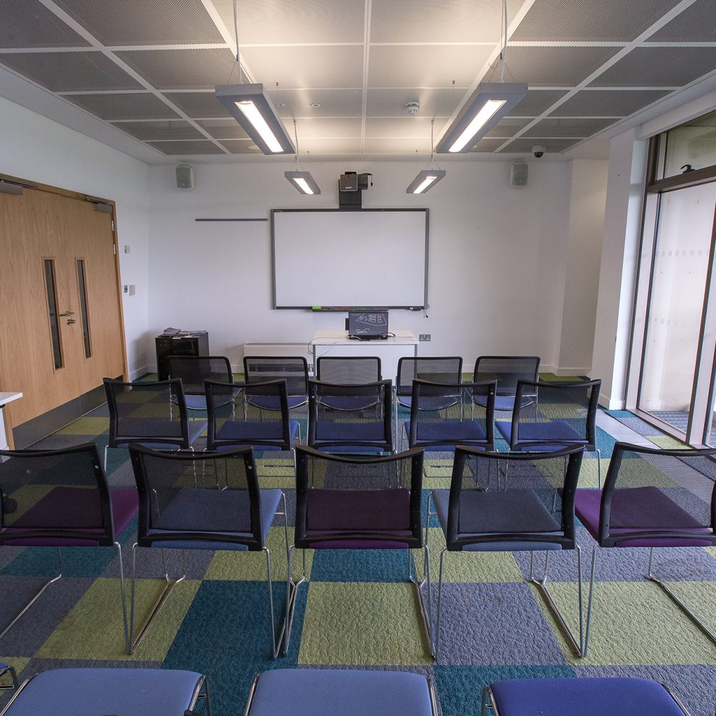 Large, bright meeting room with big window and chairs in rows and projector screen at far end
