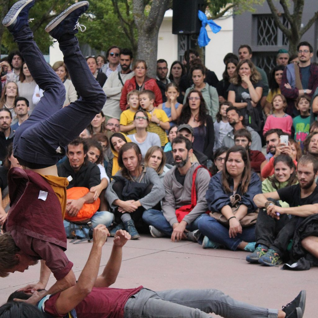Two male dancers, one doing a handstand on the other, watched by a large crowd.