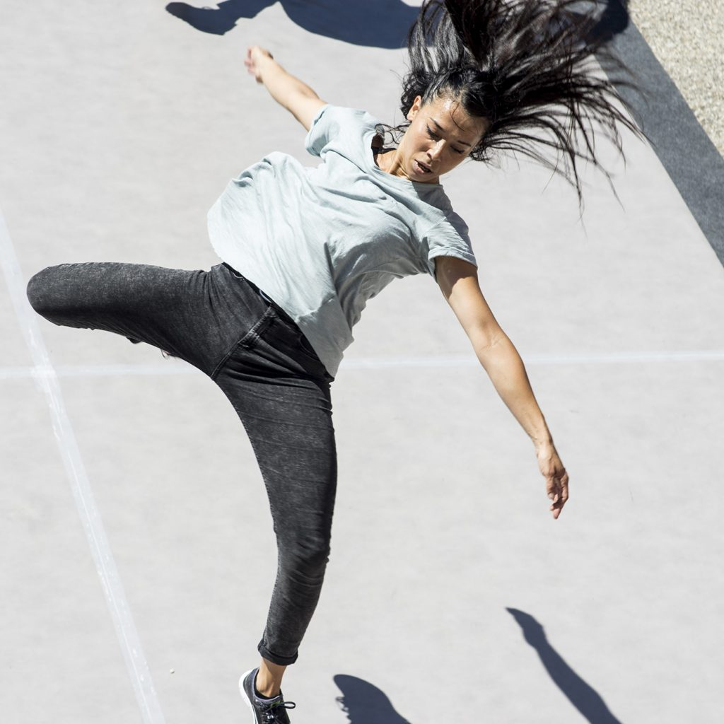 A woman leaps in a dance move. Shot from above her.