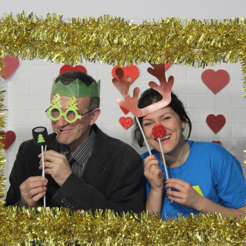 Displace yourself Christmas party: participants pictures in a gold tinsel frame with silly festive props.