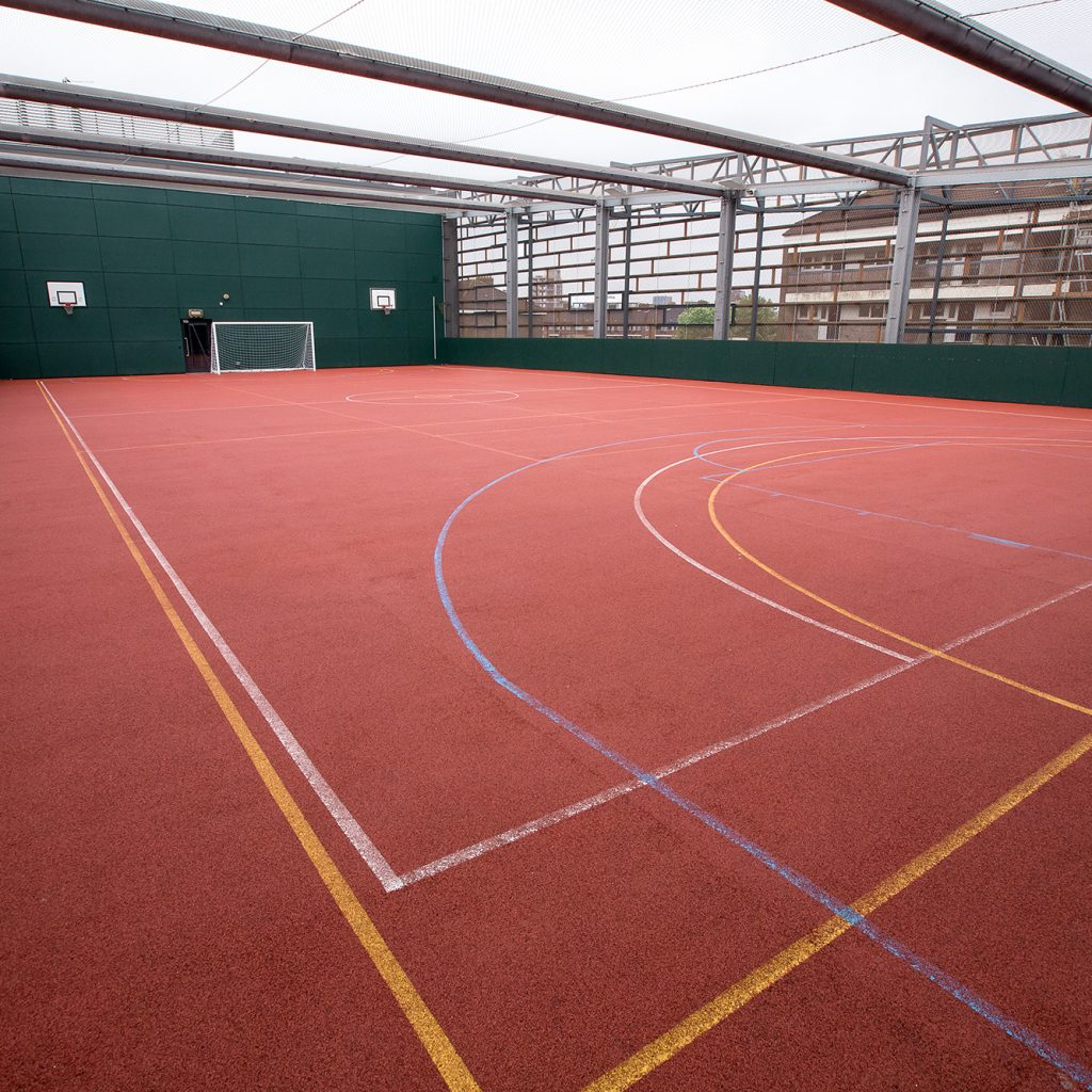 The rooftop Ballcourt at Deptford Lounge.: red ballcourt marked out with lines for sports with a football goal net at the far end.