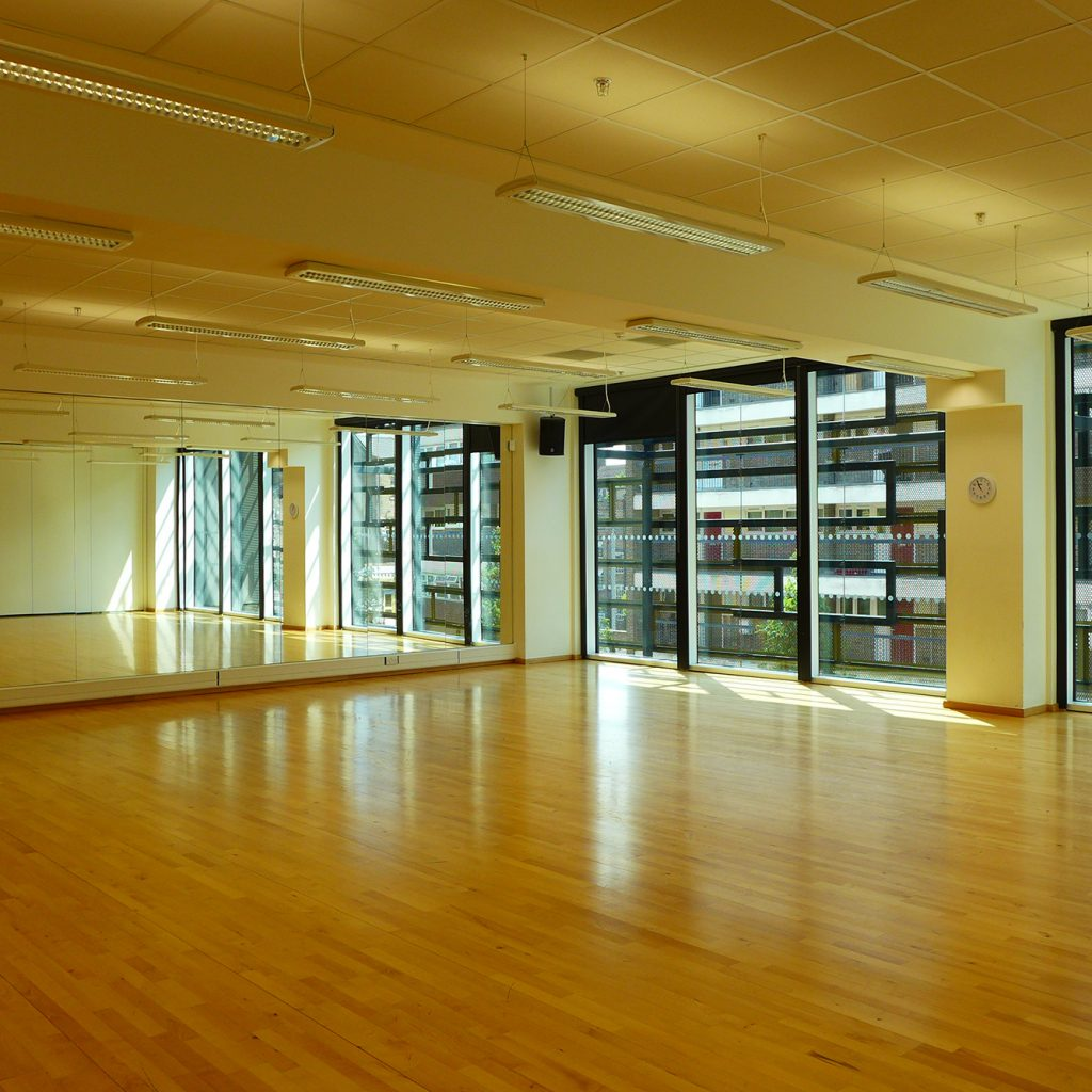 Large, mirrored, rehearsal room with wooden floor.