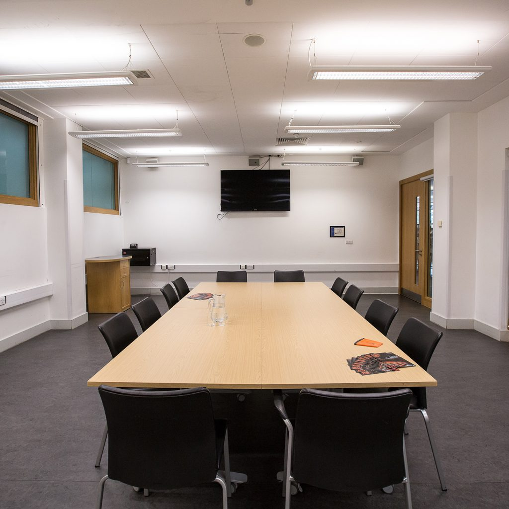 Spacious meeting room with large TV screen at far end and board room style table and chairs with