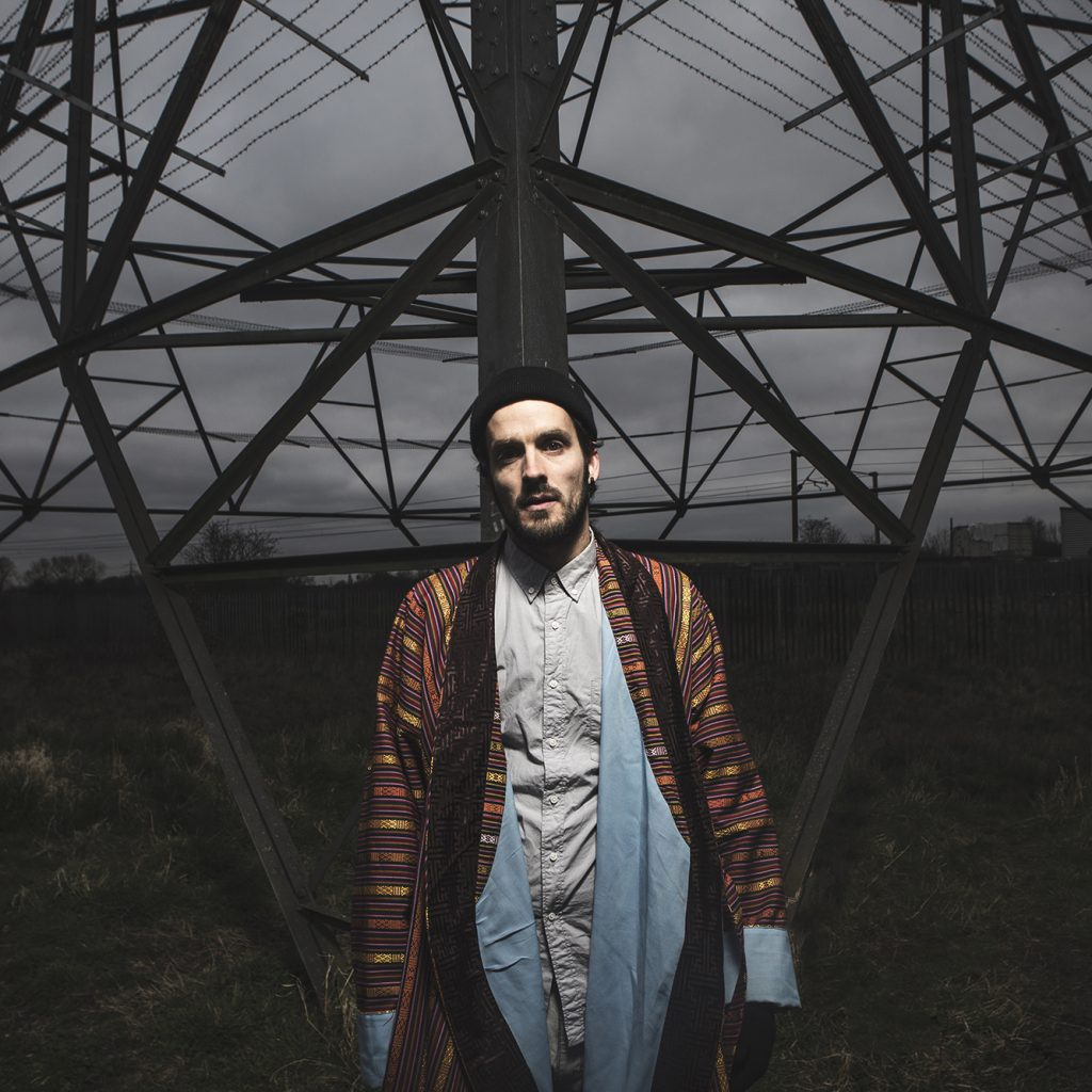 Dizraeli stands in front of a huge electricity pylon under a moody, grey sky.