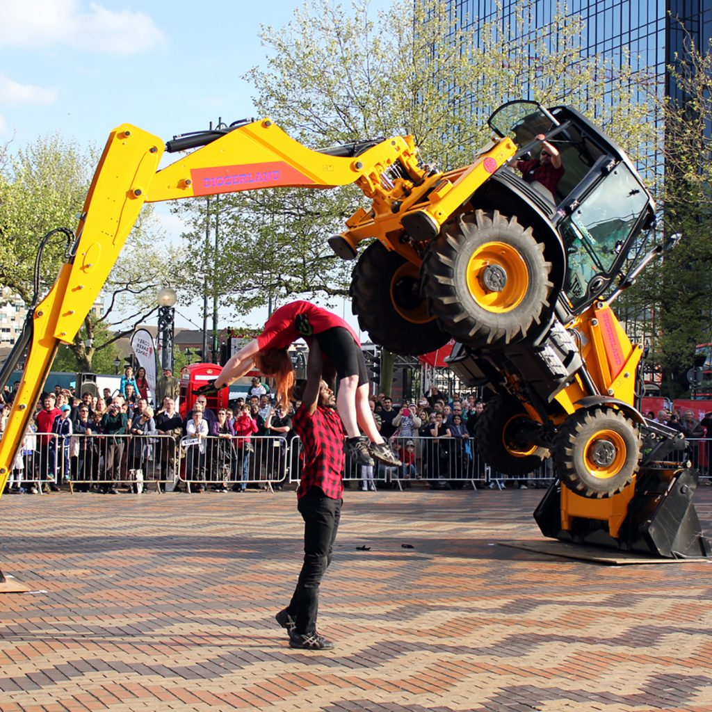 Two dancers in red and black perform together in front of an orange ditch digger. They are in an urban location and a large crown look on.
