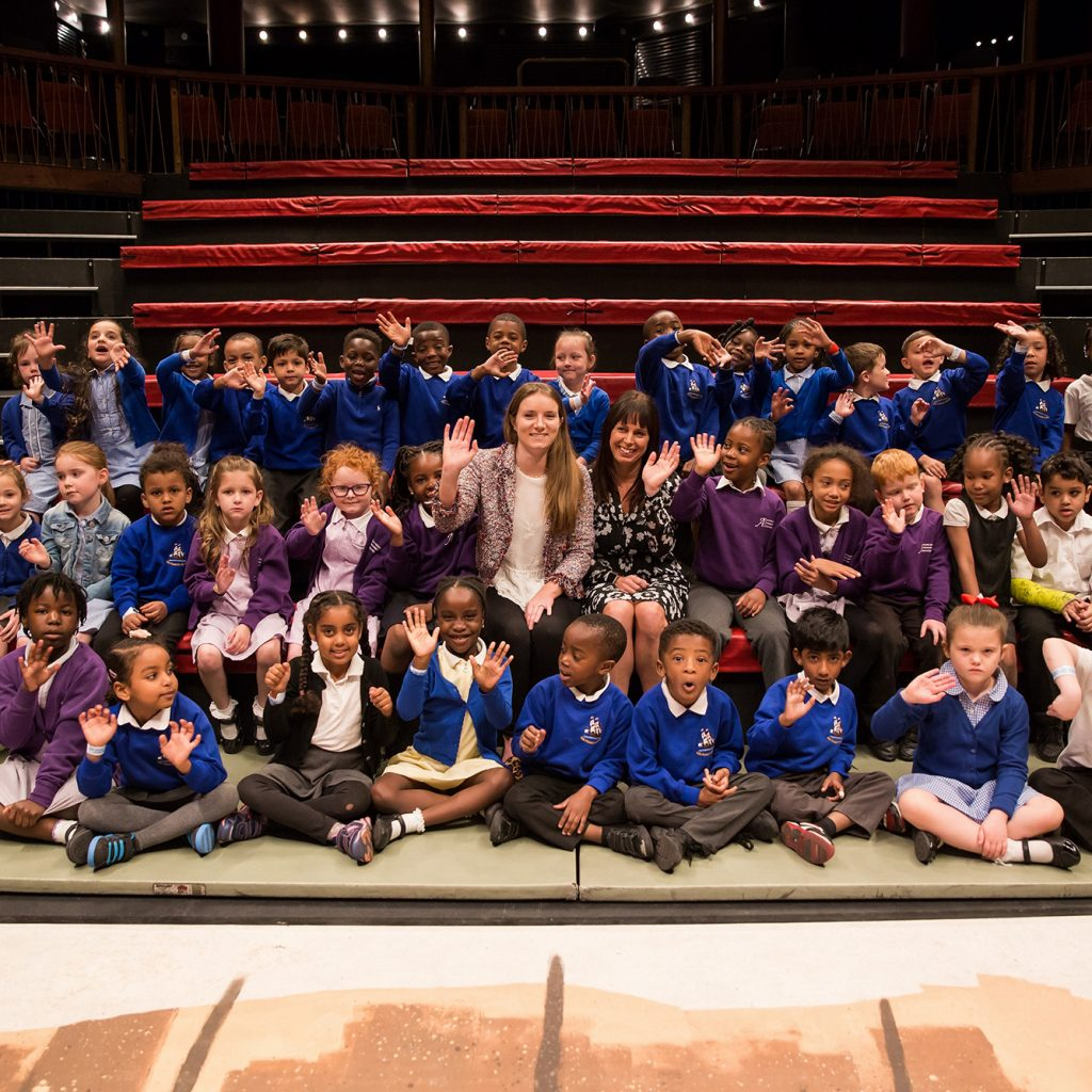 Large group of young school children with sponsors from Antholody, seated smiling and waving at the camera in the Albany theatre.