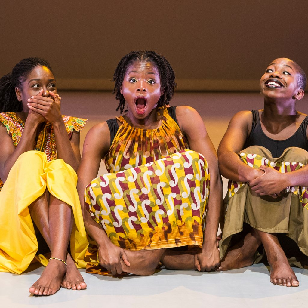Three young women of colour in yellow and black dresses sit side by side on the floor. They are laughing or smiling.