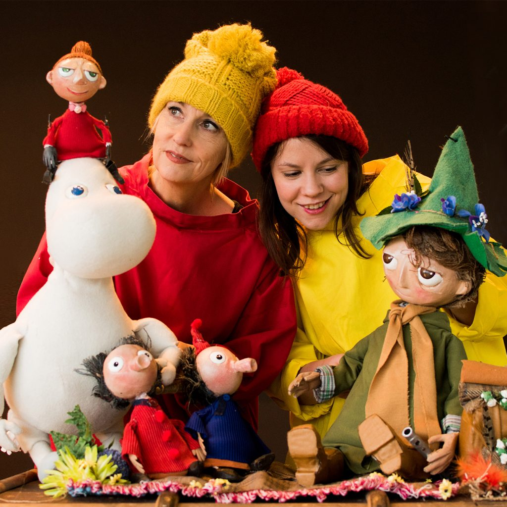 Two women pose with puppets of people and a Moomin.