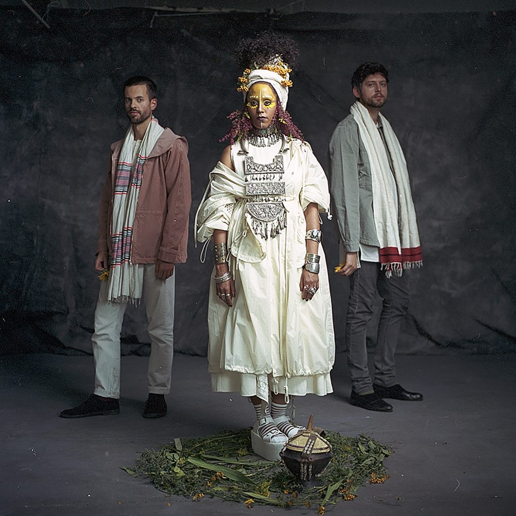 Image of Hejira - a woman with her face painted yellow and two men behind her.