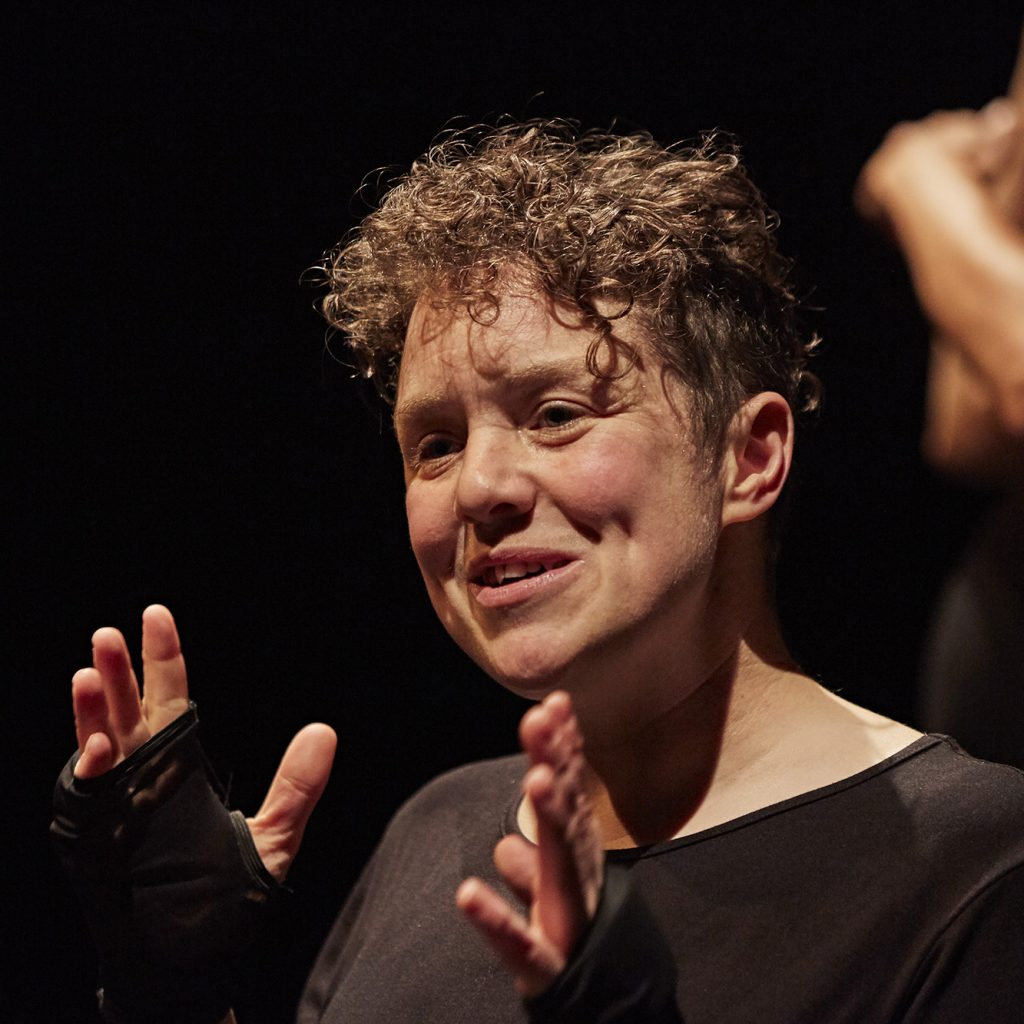 Picture of Jess Thom - a white woman in her 30s with short curly hair, wearing a black T-short and holding her hands up as she talks animatedly.