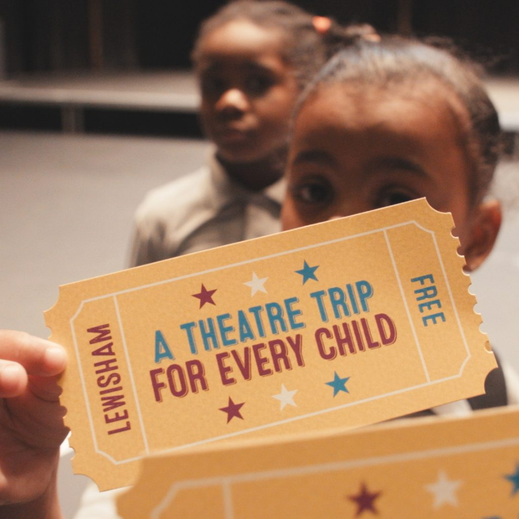 Children holding up postcards to the camera for A Theatre Trip for Every Child