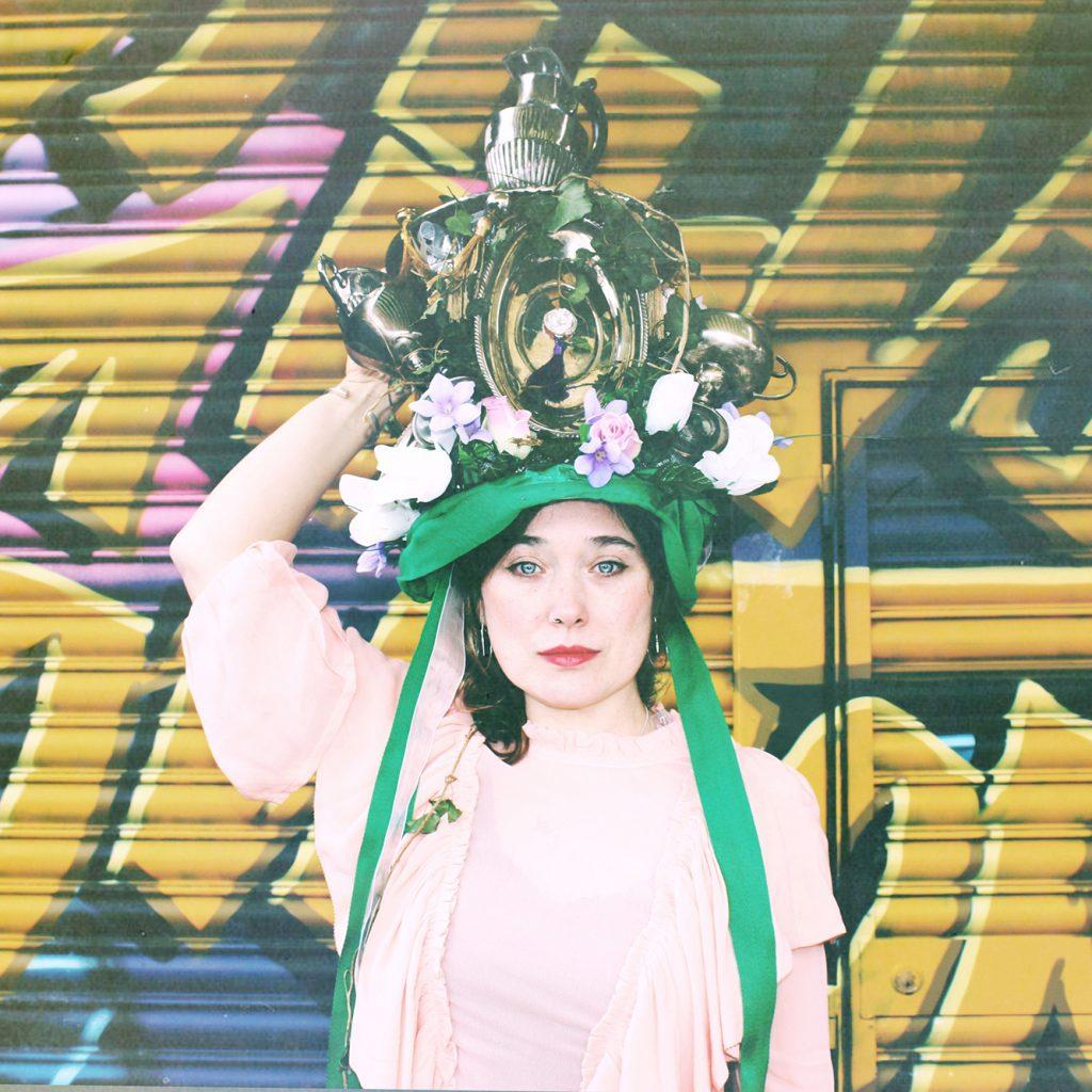 Lisa Knapp in a flamboyant hat, looking straight at the camera.