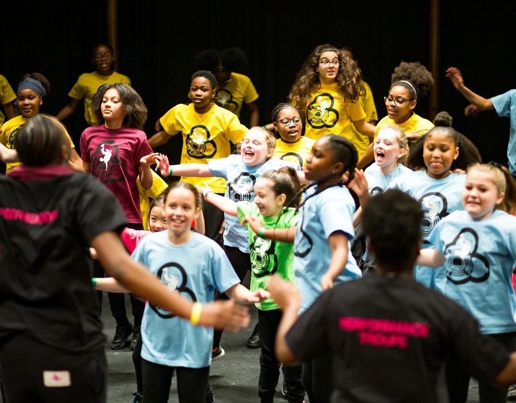 Image of a group of young people in different colour t-shirts are dancing and laughing.