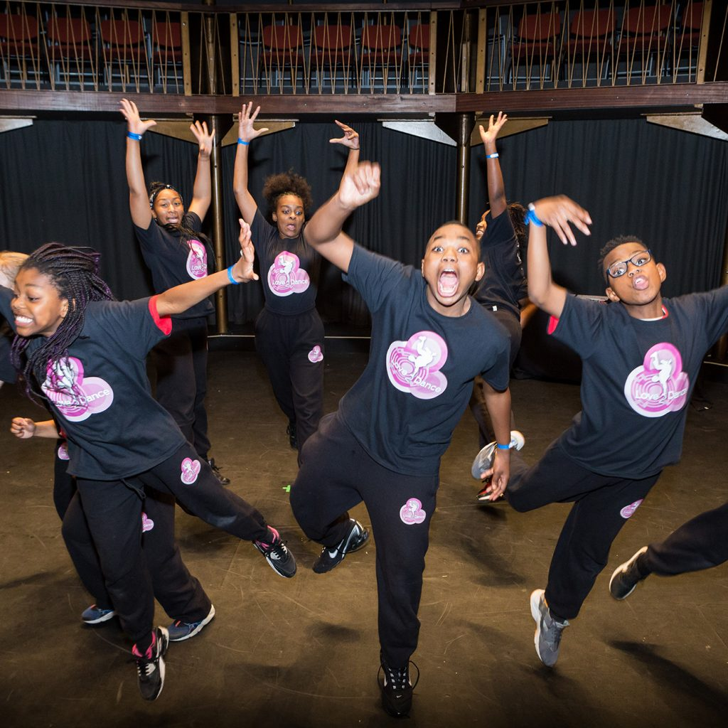 Young performers in black and pink T-shirts dance on the Albany stage.
