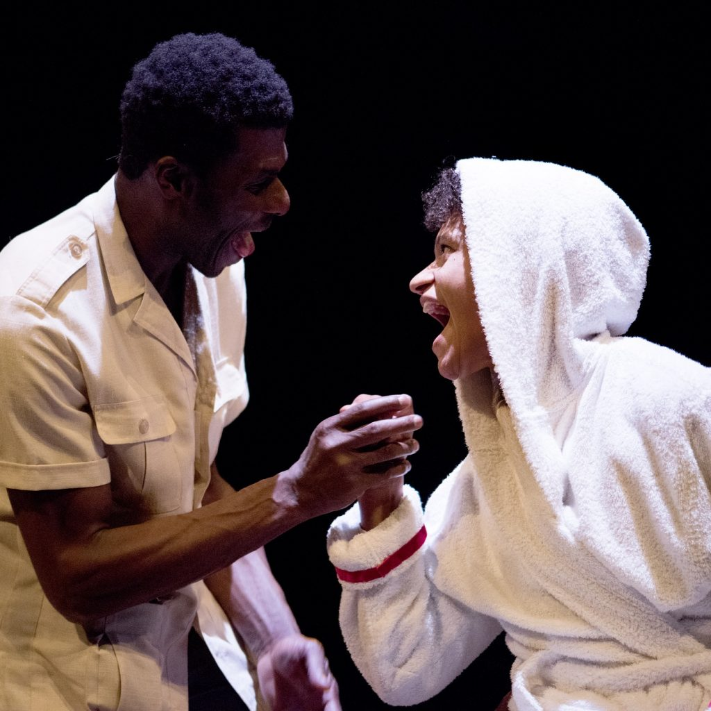 Two actors clasp hands on a black background. One (female) is wearing a hooded dressing gown, the other (male) is in a karky shirt.