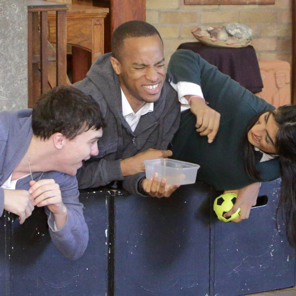 Three actors lie on a row of black wooden boxes. They are smiling or laughing.
