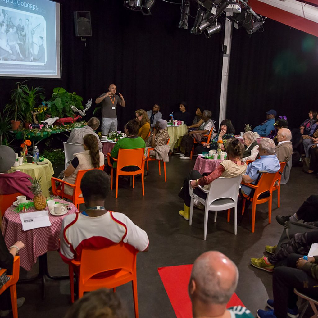 Lots of people sit in a large performance studio around tables and in a row of seats. They are about to watch a film on a large screen at the front of the room. There is a display with sculptures and a model forest at the front of the room.