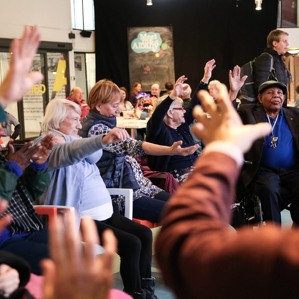 A group of older people sit in a circle in the Albany café with their arms in the air, during a movement session,