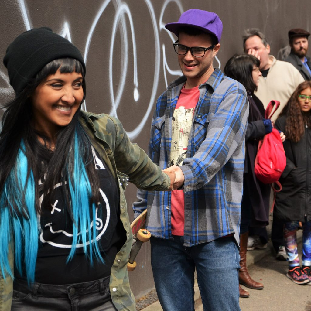 A young woman in a black woolly hat with black and bright blue hair grins as she leads a young man by the hand up an urban street. A small crowd of all ages look on.