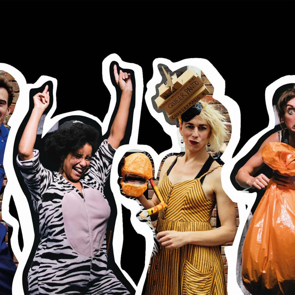 A performer in a blue jumpsuit smiling, a performer in a zebra onesie dancing, a performer in a yellow striped dress and an elaborate cardboard hat made of books, a performer holding an orange bin bag looking shifty