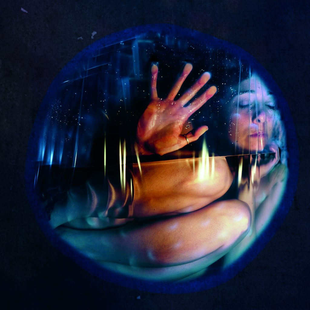 A woman is curled up inside a cramped, see through sphere with her eyes shut.