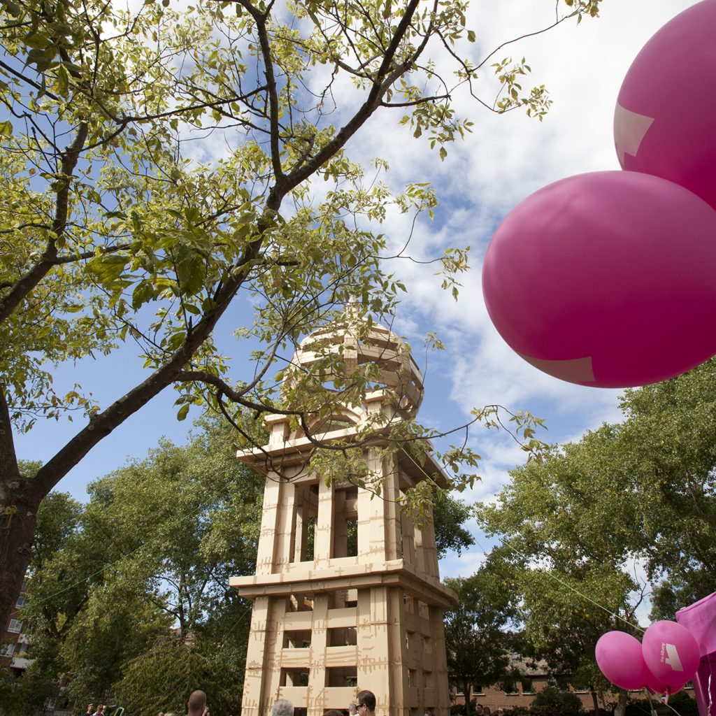 Blue sky, pink balloons and a huge cardboard tower built by members of the public in the Albany garden for a project called The People's Tower