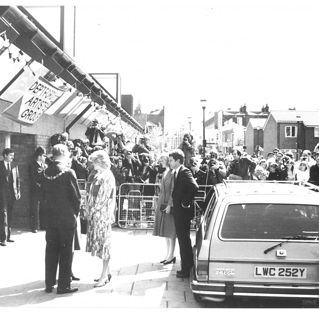 Black and white image: Princess Diana at the Albany entrance. Barriers and crowds in the background.