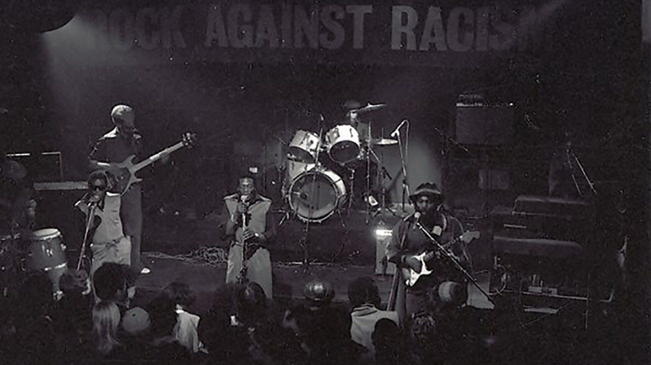 Musicians on stage and the crowd at a Rock Against Racism gig.