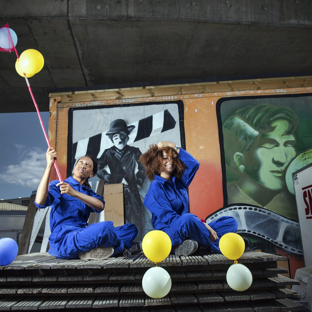 Two young people in blue boiler suits sit atop a pile of wooden pallets. There is a snack truck beside them and there are yellow and white balloons.